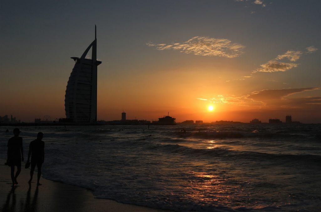 Stranden bredvid Burj Al Arab är perfekt för att kolla solnedgången. Turist i Dubai.
